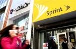 7888-a-woman-using-a-cell-phone-walks-past-t-mobile-and-sprint-st